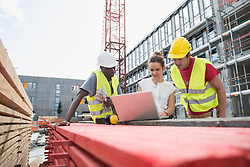 Architect using laptop with construction worker at building site, Munich, Bavaria, Germany