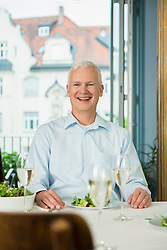 Portrait of mature man sitting at table, smiling