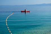 Mooring line and buouy with sea kayak, beach at Zlatni Rat, near Bol, island of Brac, Croatia