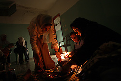 Subhia Al-Athamneh, 52, and relatives eat by candle light in their home, which was damaged after Israeli airstrikes targeting a neighbor went astray, Beit Hanoun, Gaza Strip, Palestinian Territories, Nov. 16, 2006.  According to Human Rights Watch, since September 2005, Israel has fired about 15,000 rounds at Gaza while Palestinian militants have fired around 1,700 back.