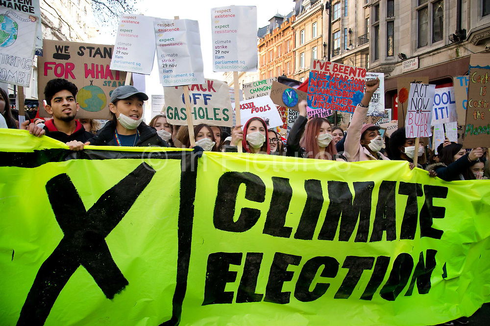 Global Climate Strike in Westminster, London, UK on November 29th 2019. Young people take part in a Friday protest, part of a global youth strike to highlight the climate emergency, with a banner saying Climate election leading the demonstration.