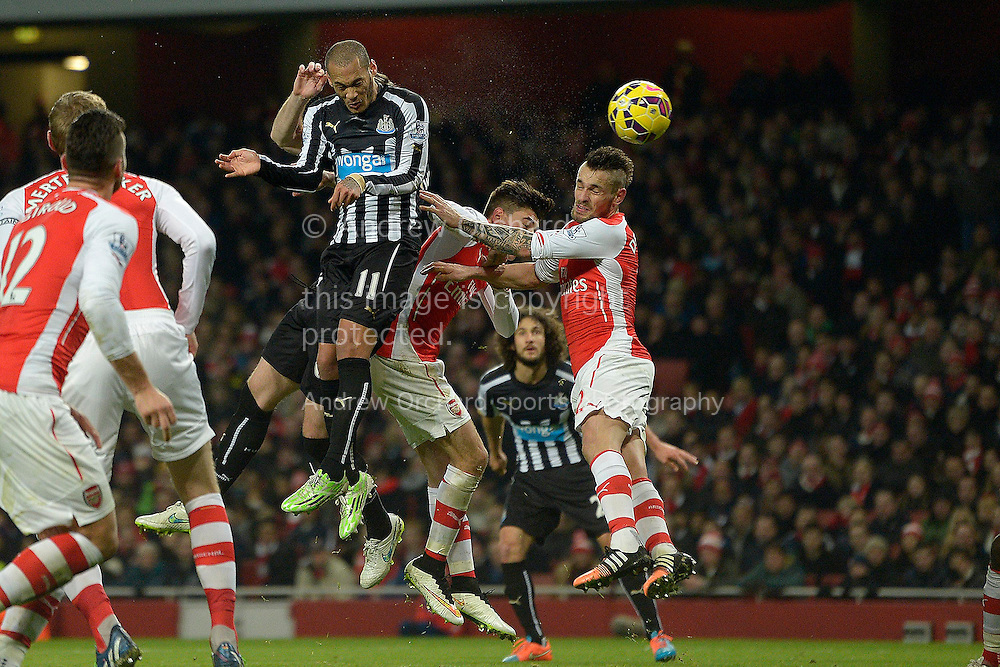 Yoan Gouffran of Newcastle United heads the ball from a corner. Barclays Premier league match, Arsenal v Newcastle Utd at the Emirates Stadium in London on Saturday 13th December 2014.<br /> pic by John Patrick Fletcher, Andrew Orchard sports photography.
