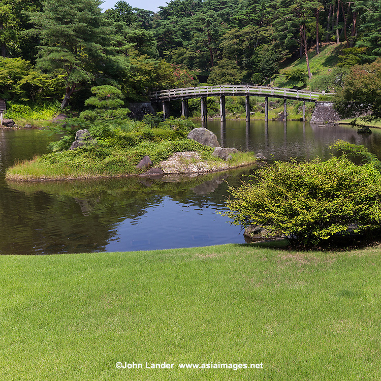 Niji-no-Sato Japanese garden, makes use of nature and surrounding land forms with an abundance of trees and flowers blooming in season, surrounded by a pond on which is a wooden Japanese arched bridge.