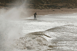 © Licensed to London News Pictures. 27/04/2019. West Bay, UK. People walking on the beach at West Bay in Dorset feel the force of storm Hannah as winds and rain hit the coast. Photo credit: Jason Bryant/LNP