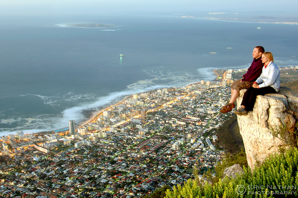 A couple observe the dusk view of Robben Island and Cape Town's Atlantic seaboard from the summit of Lion's Head.