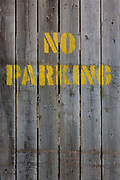 Detail of a No Parking stencil lettering on wooden slats in south London. Stenciled in yellow letters, the words habe been sprayed on to the faded old panels of a fence in a south London industrial yard.