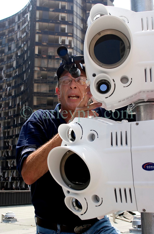 10 Sept 2005. New Orleans, Louisiana. Hurricane Katrina aftermath. <br /> Ben Smith aligns infra red free space optic radio links as the process of resurrecting the city begins in earnest.<br /> Photo; ©Charlie Varley/varleypix.com
