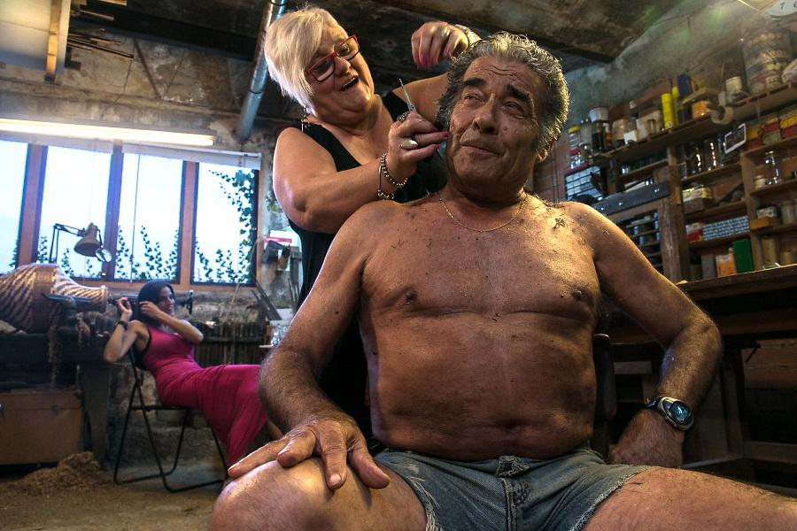 /ES/ Emilio bromea con su vecina Antonia que ha venido a cortarle el pelo en el salón de peluquería que ha improvisado en medio de su taller.