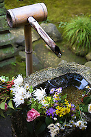 Floral Water Fountain Tsukubai colourfully festooned with a flower arrangement at Korin-in Garden at Daitokuji Temple.  Korin-in was a family temple of the Maeda Family. The main temple, the front gate and the entry gates are designated Important Cultural Properties by the Japanese government and are typical Zen style architecture in the Muromachi period.