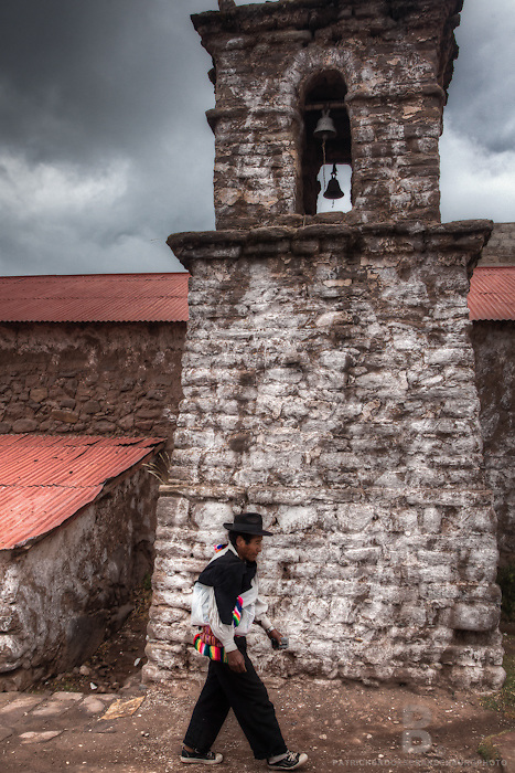 A known leader of Amantaní Island on Lake Titcaca, Luciano, walks by in traditional clothing worn by the leaders of the island such as black sombrero, passing by an adobe mud brick church and church bells.