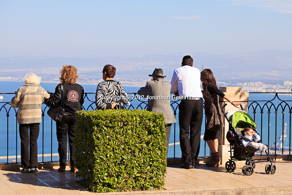 Sabbath sightseers on a scenic overlook on Haifa's Mount Carmel take in the view of the Bahai temple and gardens, city, port and harbor below. WATERMARKS WILL NOT APPEAR ON PRINTS OR LICENSED IMAGES.