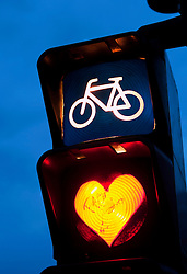 Detail of red cycle traffic stop light painted with love heart in Berlin Germany