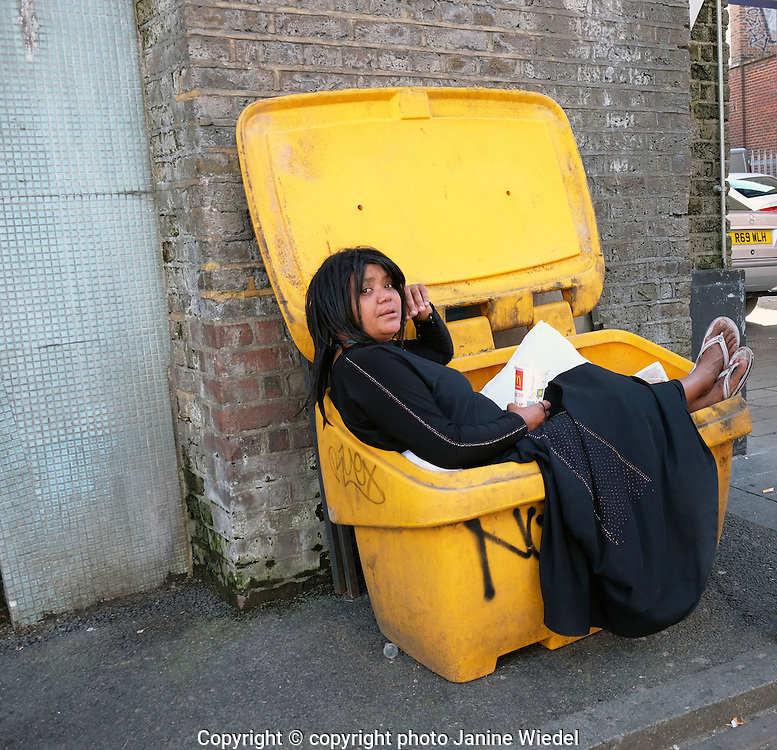 Woman sitting in a rubbish bin  on the street in Streets of Brixton South London