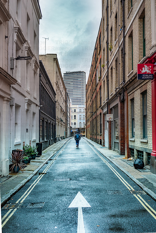 Narrow street in Bloomsbury, London looking towards the Centre Point highrise building with male figure walking away.
