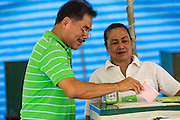 03 MARCH 2013 - BANGKOK, THAILAND: .A man drops his completed ballot into the ballot box at a polling place in Benchasiri Park in Bangkok. Bangkok residents went to the polls Sunday to elect a new governor. Voter turnout was expected to be heavy for a local election. Pongsapat Pongchareon, the Pheu Thai candidate is thought to hold a slight lead over Sukhumbhand Paribatra, the Democrats' candidate. There are a total of 25 candidates in the election but only Pheu Thai and the Democrats are given a chance of winning.     PHOTO BY JACK KURTZ