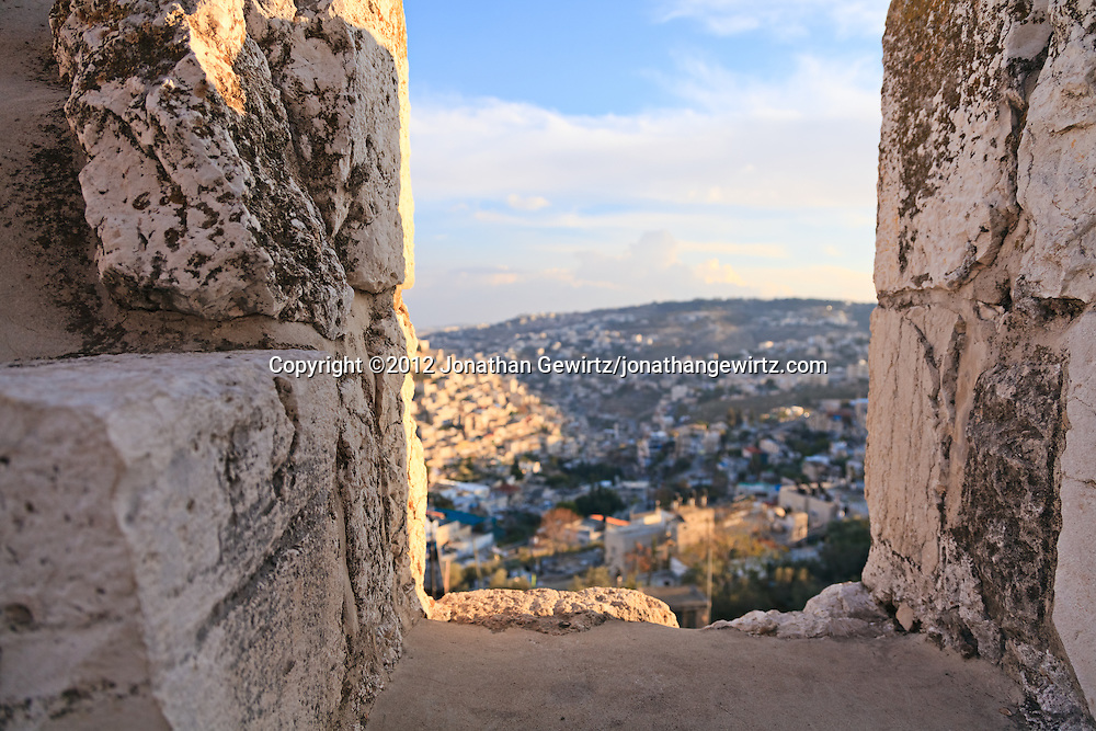 Closeup view of a battlement on the top of one of the exterior walls of the Old City of Jerusalem. The village of Silwan is visible through the gapin the wall.
