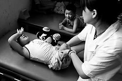 Chun Rui Xia, 8, left, of Mianzhu, cries as a nurse massages her amputated leg at the Sichuan Limbs Maim Restoration Centre in Chengdu, Sichuan in China. 21 of her classmates were killed due to the earthquake.