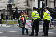 Metropolitan Police officers ask a protester with a loud hailer to move out of the road during a protest opposite Downing Street by leaseholders and tenants living in unsafe homes on 15th July 2021 in London, United Kingdom. Some leaseholders are faced with crippling costs to fix safety issues and they called on the government to ensure that their homes are made safe from fire as a matter of priority, to make interim payments and to cover fire safety remediation costs and to find a solution with mortgage lenders which enables them to move on with their lives.