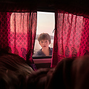 A boy looks inside his camping car - camper van in the early morning.