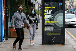 © Licensed to London News Pictures. 26/12/2020. London, UK. Members of public wearing a face coverings in north London walk past the government's 'Coronavirus Tier 4 - Stay Home' publicity campaign poster as many parts of the UK entered the highest level of COVID-19 restrictions on Boxing Day after mutated COVID-19 strains continue to spread around the country. Prime Minister, Boris Johnson refused to rule out a third national lockdown in the New Year. Photo credit: Dinendra Haria/LNP