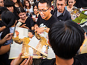 17 OCTOBER 2016 - BANGKOK, THAILAND:  A man was swamped by takers when he gave away portraits of Bhumibol Adulyadej, the late King of Thailand, at Sanam Luang in central Bangkok. Thai King Bhumibol Adulyadej died Oct. 13, 2016. He was 88. His death comes after a period of failing health. Bhumibol Adulyadej, was born in Cambridge, MA, on 5 December 1927. He was the ninth monarch of Thailand from the Chakri Dynasty and is also known as Rama IX. He became King on June 9, 1946 and served as King of Thailand for 70 years, 126 days. He was, at the time of his death, the world's longest-serving head of state and the longest-reigning monarch in Thai history.       PHOTO BY JACK KURTZ