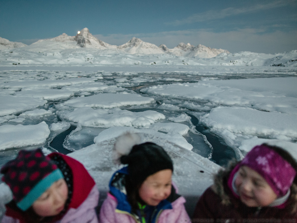 Moonrise in the afternoon. Sunday family fishing trip (arctic cod) in ice holes, with hunter Tobias Ignatiussen, his wife Silba, daughter Gerda and two friends Naima and Laila.<br /> Life in and around the Inuit settlement of Tasiilaq (population of 2000), in East Greenland.