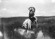 Cheyenne Indian, wearing headdress, on horseback, 1905. Photograph by Edward Curtis (1868-1952).