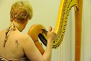 Female Harpist tunes her harp