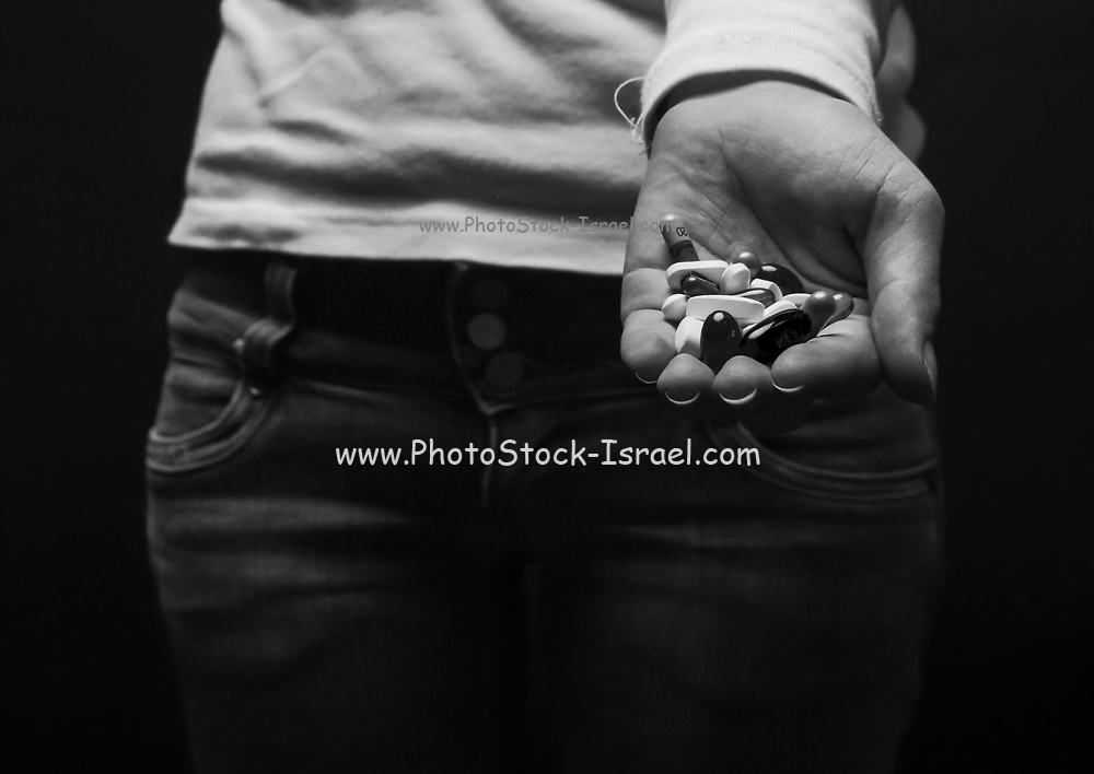 Teenage suicide - youth holds a handful of pills and medicine