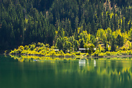 A fisherman on boat passes a small lake side home along the still waters of the Gros Ventre Lower Slide Lake in Wyoming, reflecting the sunlit early autumn yellows and light green hues.