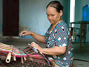 A Hindu Cham woman weaves cotton and silk fabric on a back-strap loom at home in My Nghiep village, Ninh Thuan province, Central Vietnam.  The resulting fabric is used to make the traditional sarong style skirt worn by Cham women on special occasions or sold to local customers in the village. The Cham people are remnants of the Kingdom of Champa (7th to 18th centuries) and are recognised by the government as one of Vietnam's 54 ethnic groups.