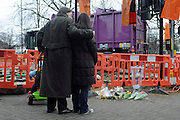 © Licensed to London News Pictures. 25/02/2010. London, UK. The Inquest opens today, 14th May 2012, into the death of a baby fatally injured by a falling lamp post. Tommy Hollis died on February 25 2010, a day short of his first birthday and two days after the incident in Chiswick, west London. FILE PICTURE: A couple look at flowers left at the scene. Photo credit : Stephen Simpson/LNP