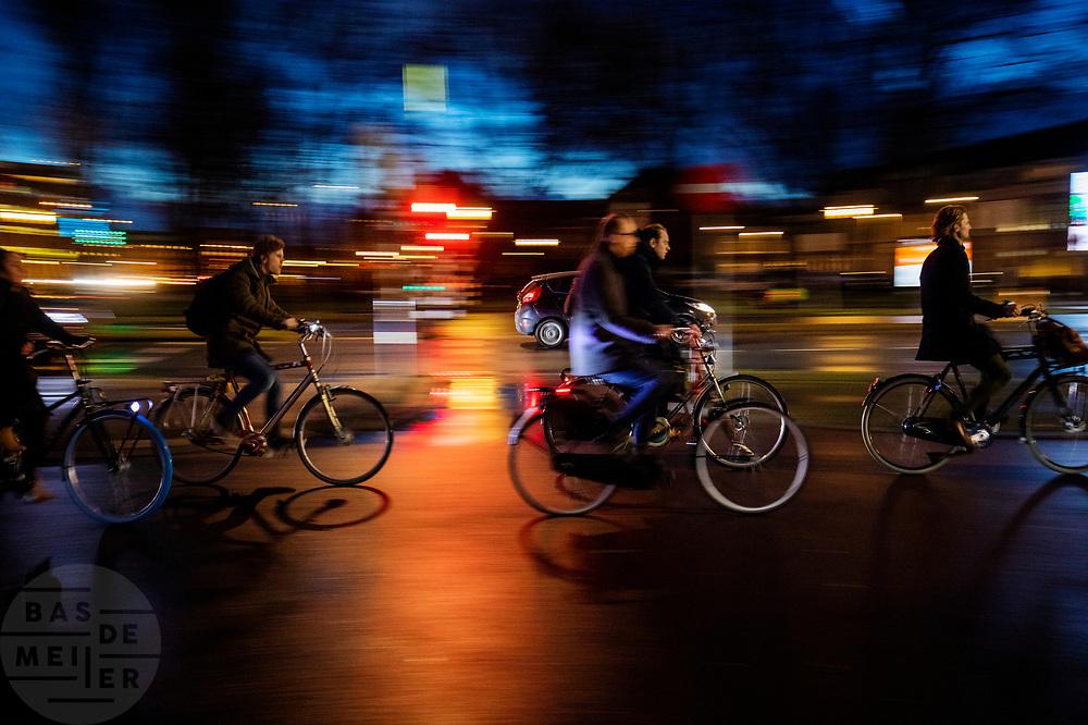 Fietsers rijden 's avonds door Utrecht. De straten zijn nat van de regen.<br /> <br /> Cyclists in Utrecht on an evening. The streets are wet due to the rain.