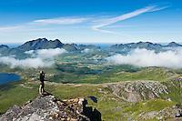 Photographer takes photos of scenic mountain landscape from summit of Justadtind, Vestvagoy, Lofoten islands, Norway