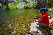 Hiker purifying water at Fern Lake, Ansel Adams Wilderness, June Lake, California USA