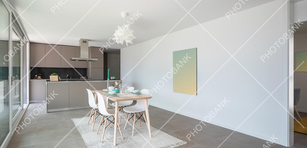 Designer set table. Behind the modern designer kitchen with island. Nobody inside
