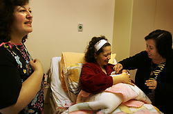 Mary Kheir, is held by her mother and blessed with the sign of the cross by a family friend at Al-Dibs Maternity Hospital in Bethlehem, Palestinian Territories, Nov. 14, 2004. The baby, born into a Christian family, is the first for the Kheir family.