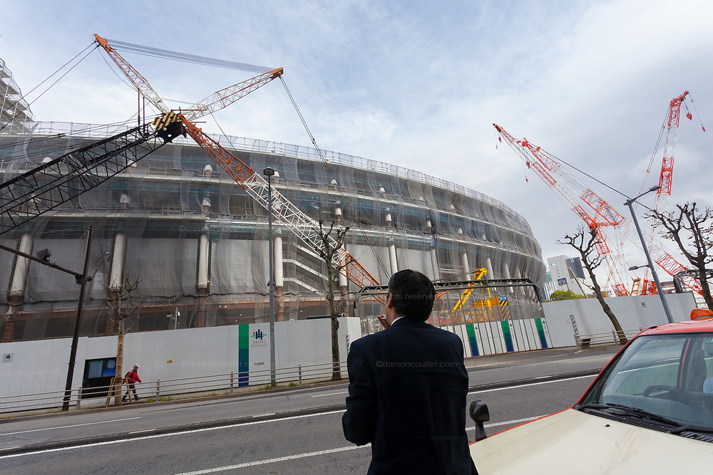 A Taxi driver takes a smoke break as he watches the construction site for the 2020 Tokyo Olympic stadium in Gaiemmae, Tokyo, Japan. Friday April 6th 2018