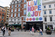 As Britain enters a period of deep recession, with some shops closing either temporarily or permanently as the economic downturn caused by the Covid-19 pandemic cuts hard, people continue to come to the West End to Covent Garden, under a large scale sign reading Love Joy and Hope on 13th August 2020 in London, United Kingdom. The Office for National Statistics / ONS has announced that gross domestic product / GDP, the widest gauge of economic health, fell by 20.4% in the second quarter of the year, compared with the previous quarter. This is the biggest decline since records began. The result is that Britain has officially entered recession, as the UK economy shrank more than any other major economy during the coronavirus outbreak.