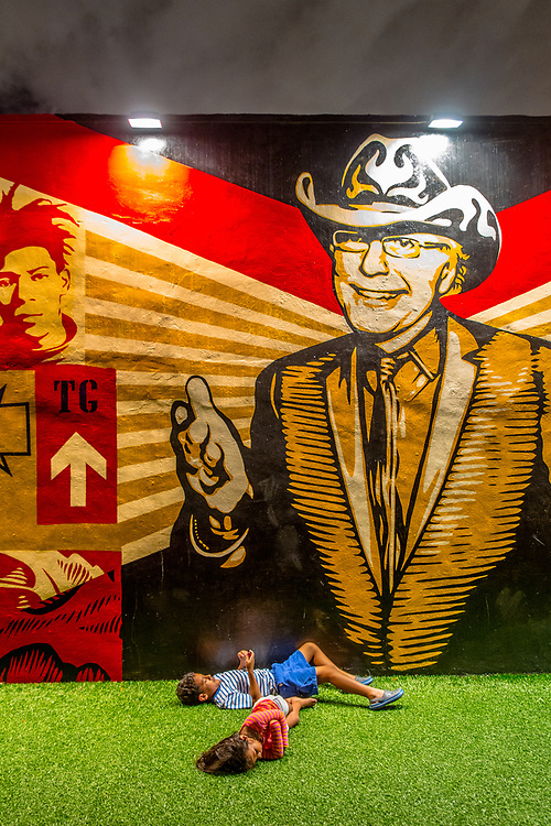 Kids sprawl in front of a mural by Visionary Wynwood Walls founder Tony Goldman in a mural by Shepard Fairey at The Wynwood Walls