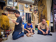 "25 MAY 2015 - BANGKOK, THAILAND:  One of Ajarn Neng Onnut's tattoo assistants prays before a day of tattooing starts in Ajarn Neng's tattoo parlor. The men to the right of him were waiting to be tattooed. Sak Yant (Thai for ""tattoos of mystical drawings"" sak=tattoo, yantra=mystical drawing) tattoos are popular throughout Thailand, Cambodia, Laos and Myanmar. The tattoos are believed to impart magical powers to the people who have them. People get the tattoos to address specific needs. For example, a business person would get a tattoo to make his business successful, and a soldier would get a tattoo to help him in battle. The tattoos are blessed by monks or people who have magical powers. Ajarn Neng, a revered tattoo master in Bangkok, uses stainless steel needles to tattoo, other tattoo masters use bamboo needles. The tattoos are growing in popularity with tourists, but Thai religious leaders try to discourage tattoo masters from giving tourists tattoos for ornamental reasons.       PHOTO BY JACK KURTZ"