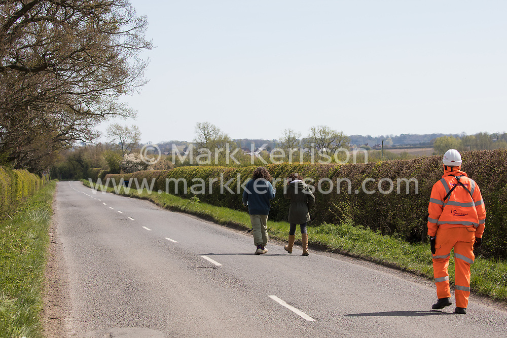 A HS2 security guard follows two Stop HS2 activists monitoring mature oak tree and hedgerow clearance works for a temporary access road for the HS2 high-speed rail link on 26th April 2021 in Quainton, United Kingdom. Environmental activists continue to oppose the controversial HS2 high-speed rail link from a series of protection camps along its Phase 1 route between London and Birmingham.