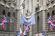 The flags of right-wing supporters of the anti-Islam activist Tommy Robinson real name Stephen Yaxley-Lennon and former leader of the now-banned English Defence League gather outside the Central Criminal Court The Old Bailey on 23rd October 2018, in London, England. Around a thousand gathered in the street specially cordoned off by City of London police as Robinson appeared before Nicholas Hilliard, the recorder of London, for a contempt hearing at the Old Bailey during which he was again bailed before the case was referred to the attorney general.