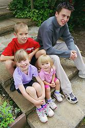 Group of children sitting outside on steps,