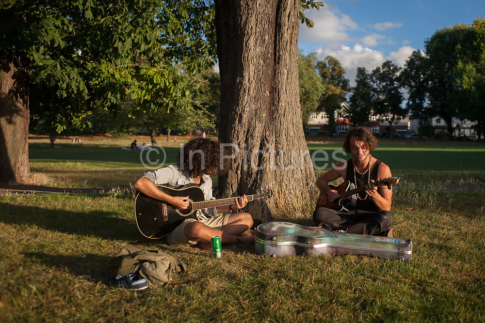 Two musicians practice their songs in late afternoon sunshine in Ruskin Park, on 8th September 2016, south London borough of Southwark, England UK. The young men are from a band called Psychedelic Pirates who, according to their card, are on a nationwide busking tour of the UK.