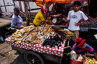 Indonesia, Sulawesi, Tomohon. Tomohon's market is a meeting place for the Minahasans. People come from all over the Minahasa region to buy and sell food and other goods. Some may call parts of the assortment bizarre. Here a selction of fruit bats, or flying dogs, and dried fish.