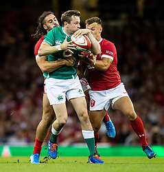 Jack Carty of Ireland looks to offload despite the attentions of  Josh Navidi of Wales<br /> <br /> Photographer Simon King/Replay Images<br /> <br /> Friendly - Wales v Ireland - Saturday 31st August 2019 - Principality Stadium - Cardiff<br /> <br /> World Copyright © Replay Images . All rights reserved. info@replayimages.co.uk - http://replayimages.co.uk
