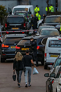 Two residents walk-in Dale Close road as Police guard a crime scene entry by the Dale Close Road, in Barnet, North London on Wednesday, Sept 23, 2020, after several police officers have been injured by a chemical substance while carrying out a drugs raid in north London. (VXP Photo/ Vudi Xhymshiti)