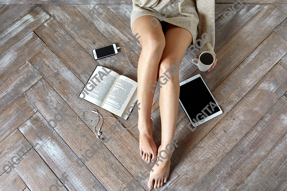 Concept of a Lazy day with a  young woman wearing a sweater sitting on wooden floor with a mobile phone, headphones, an electronic tablet and a paperback book, copy space, top view, horizontal