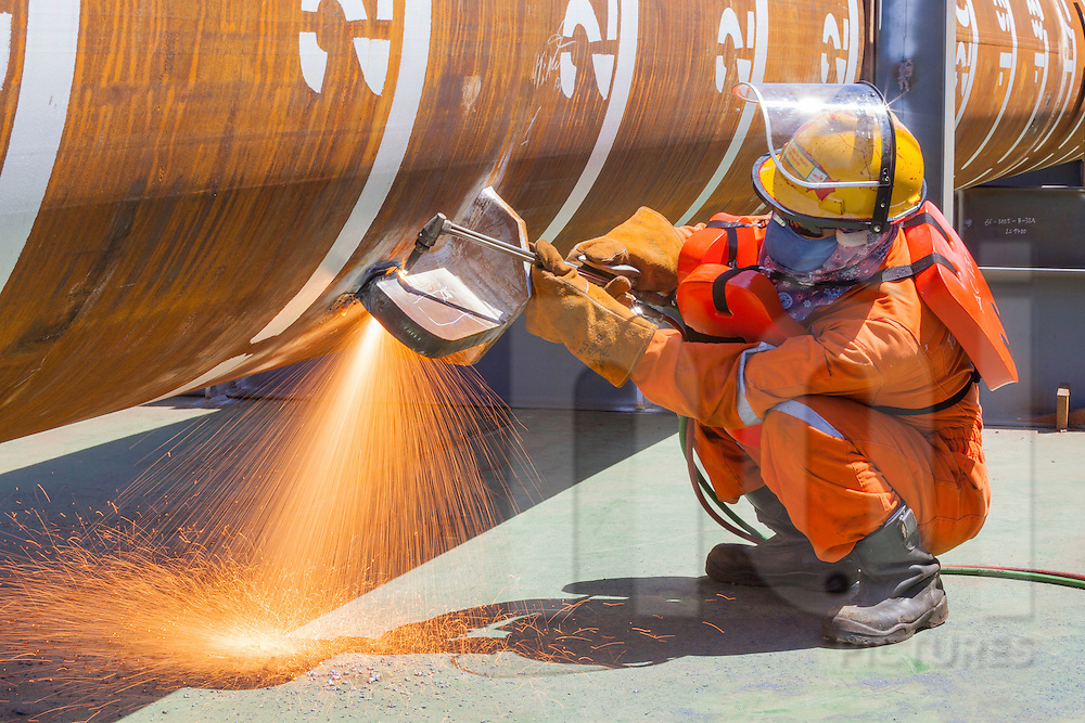 Worker operating with a blowtorch on an oil rig offshore of Vung Tau, Vietnam, Southeast Asia